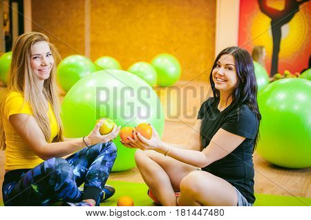 Two Young Athletic Physique Women In Gym. Fitness Girl With Fruits, Lifestyle In Losing Weight And D