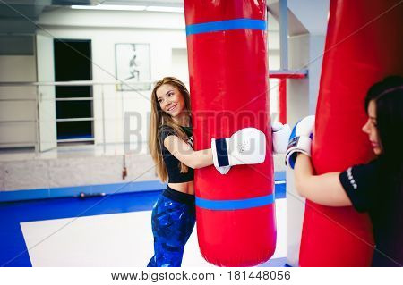 Young Woman Exercising In The Gym. Woman Hugging A Punching Bag