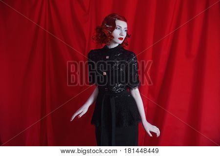 Seductive woman with red curly hair in a black seductive dress and retro makeup on a red background. Red-haired seductive girl with pale skin blue eyes a bright unusual appearance red lips and a fatal face. Noir seductive woman. Seductive model