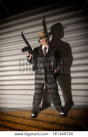 Mature man dressed as a 1940s gangster holding a machine gun, on a grey background