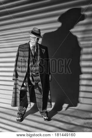Black and white image of a mature man dressed as a 1940s gangster, on a grey background