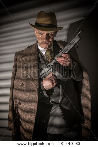 1940s male gangster holding a machine gun