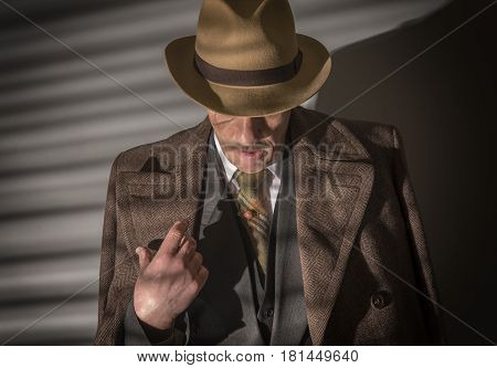 Mature man dressed as a 1940s gangster, on a grey background