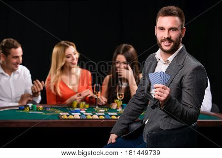 Poker players in casino with cards and chips on black background. A handsome man in the foreground, behind a game table.