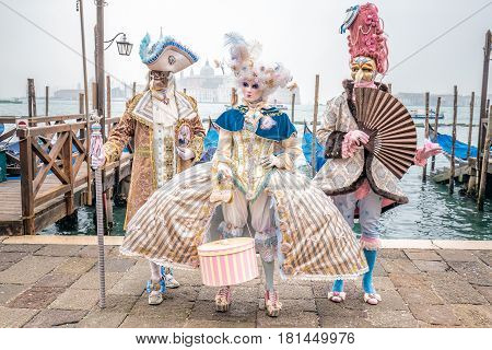 Blue and gold masked carnival costumes trio, Venice, Italy.