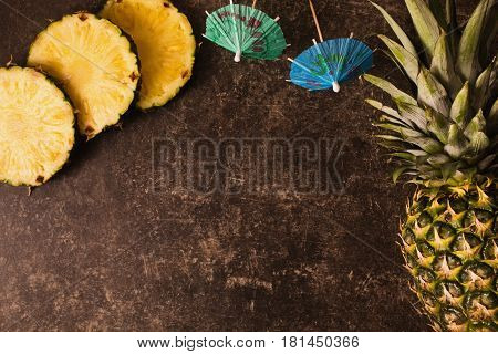 Ripe pineapple and cocktail umbrellas on a dark table with a marble texture with scratches. Cut fruit. Healthy eating. Going on a journey to the south.