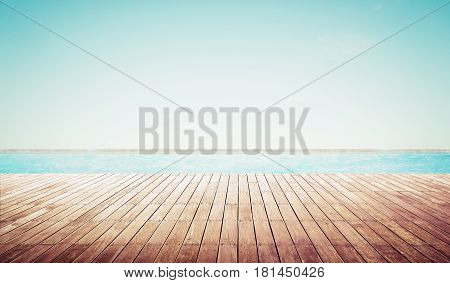 Empty wooden deck with swimming pool Beautiful minimalist pool side view with clear blue sky . Vintage filter color apply .