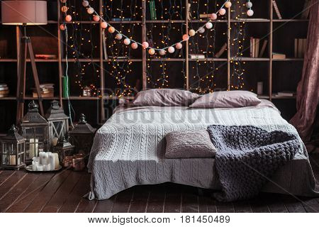 coziness, comfort, interior and holidays concept - cozy bedroom with bed and garland lights at home. A rack with books behind the bed. Candles, a lamp and a lamp stand near the bed. Plaid hand-knitted.