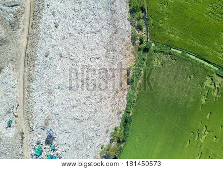 Garbage In Municipal Landfill For Household Waste With Paddy Field