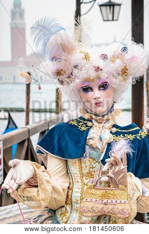 Blue and gold masked minx girl with carnaval costume, Venice, Italy.