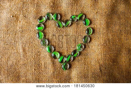 heart of transparent stones with a green tint on linen background