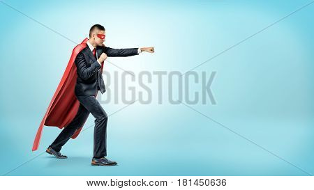 A businessman in a flowing red superhero cape and a mask throwing punches at an invisible enemy on blue background. Business and rivalry. Overcoming difficulties. Fight for success.