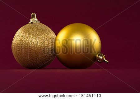 Closeup of golden Christmas balls on a red background