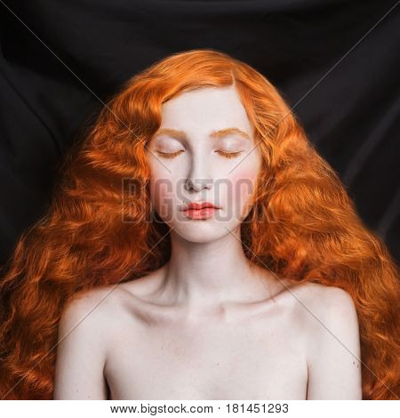 Woman with long curly red flowing hair on a black background. Natural beauty woman. Red-haired woman. Beautiful woman with red hair and pale skin. A woman on black background. Model posing in studio. Insidious wicked witch woman. Redhead woman. Woman in s