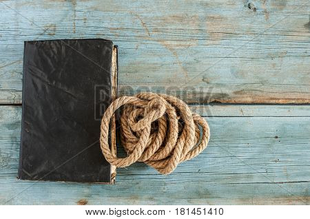 antique book and rope on wood