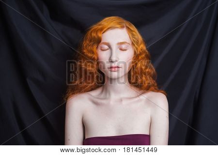Renaissance woman with long curly red flowing hair on a black background. Red-haired renaissance girl with pale skin blue eyes bright unusual appearance without makeup. Natural beauty. The girl from the era of renaissance. Renaissance model