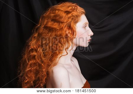 Pretty woman with long curly red flowing hair on a black background. Red-haired pretty girl with pale skin blue eyes bright unusual appearance without makeup. Natural beauty. The pretty girl from the era of renaissance. Pretty model