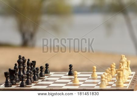White chess pieces staying against black chess pieces Chess board with chess pieces on wooden bench with river embankment background Selective focus