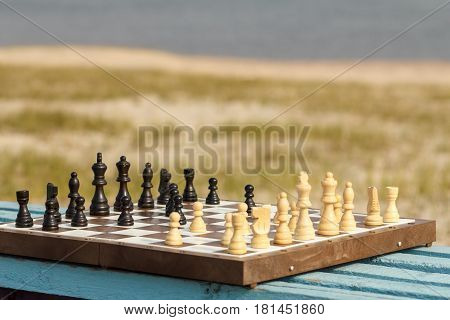 Chess board with chess pieces on wooden bench with river embankment background. Outdoors chess game