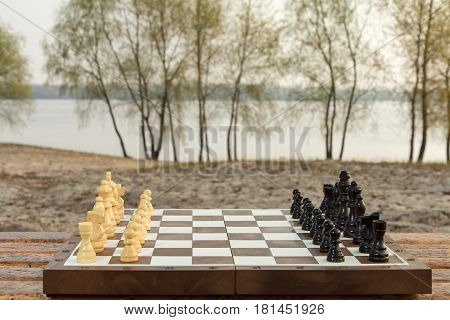 Chess board with chess pieces on river embankment. Chess game with wooden chess pieces