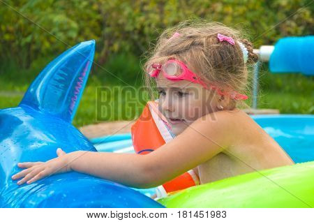 Little girl, kid, swimming in the pool, inflatable circles, afraid, sunny