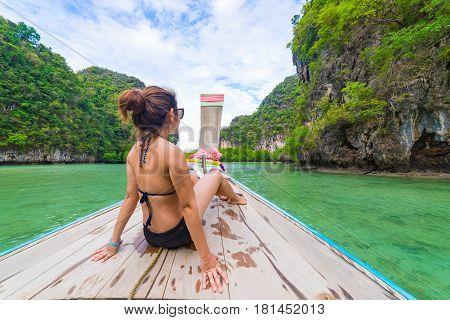 Traveler Summer concept - Beautiful woman in bikini traveling on long boat to Hong Islands in andaman sea Krabi South of Thailand.