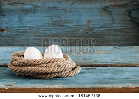 fresh egg with pile rope on wood table background