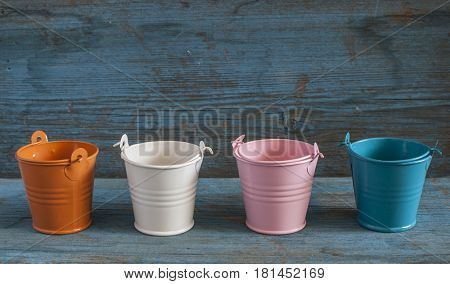 empty colorful buckets on old wooden background.