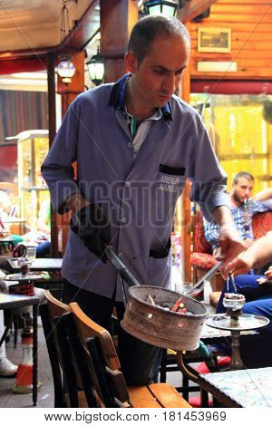ISTANBUL - CIRCA JUNE 2015: Hookah-maker replaces the coal in the guest's hookah in the Tea Garden in Istanbul close to Grand Bazaar