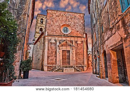 Pitigliano, Grosseto, Tuscany, Italy: cityscape at sunset of the old town with the ancient church of Santa Maria e San Rocco in the medieval village founded in Etruscan time