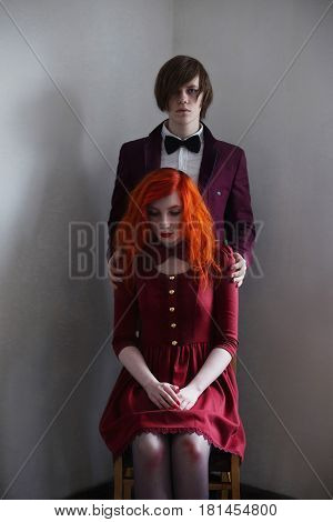 Informal guy with long hair in a jacket and a woman with long red curly hair in a red dress with bow tie on the neck on a white background holding hands. Red-haired girl with pale skin and blue eyes