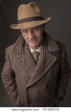 Mature man dressed as a 1940s gangster, on a dark background