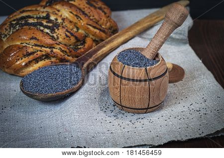 Poppy seeds in a wooden mortar next to a baked roll