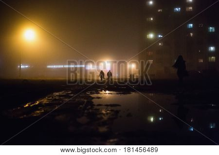 City at night in dense fog. Thick smog on a dark street. Beautiful mixed light from the street lamps. Silhouettes of people and trees. Pillars at road