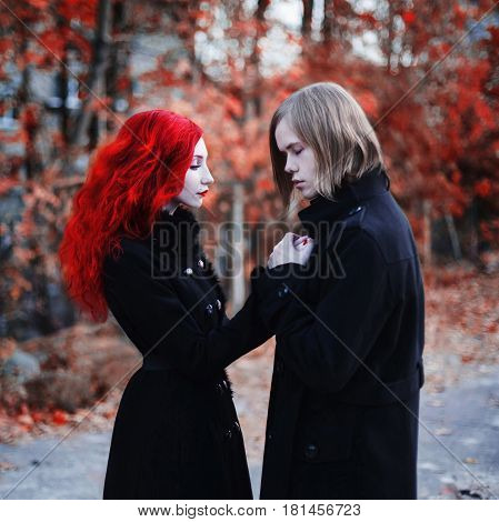 Informal guy with long hair and a woman with long red curly hair in a black coat. Red-haired girl with pale skin blue eyes with bright unusual appearance and a sweet face. Goths