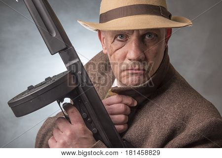 1940s male gangster holding a machine gun, on a grey smoky background