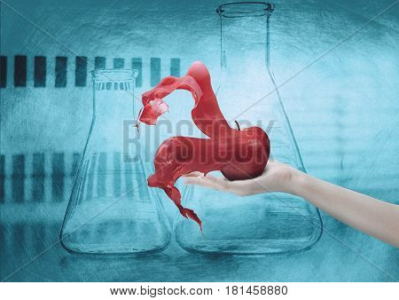 Hand holding apple disintegrating over background with scientific theme