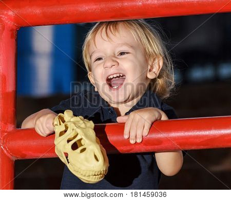 Little Blond Boy Laughing Very Happy Holding A Toy