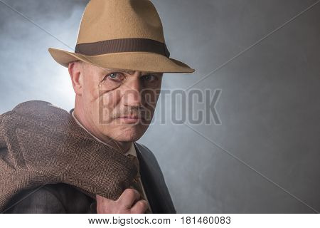 Mature man dressed as a 1940s gangster, on a grey smoky background