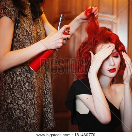 Hairdresser doing her hair with hairspray. A woman with red hair in a black dress covers her face by hand. Red-haired girl with pale skin blue eyes a bright unusual appearance red lips.