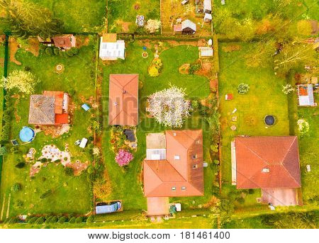 Aerial view of area for pleasant living in suburban district. Houses in beautiful gardens with blooming trees. Beautiful spring nature on Czech countryside. European landscape from above.