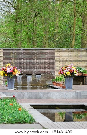 The Fountain With Flowing Water And Flowerbeds
