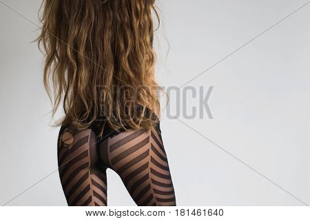 Girl with very long hair to the waist on a white background. Conceptual photography. A woman is standing back. Conceptual photography with nice ass. Women's back and ass. Ass in the underwear Beautiful ass in black lingerie
