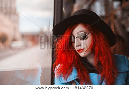 Woman with red curly hair in a blue coat and black round glasses riding on the bus. Red-haired girl in bus with pale skin and bright appearance with black hat on head and looking out the window. Street style. Ride in a bus. Bus ride concept
