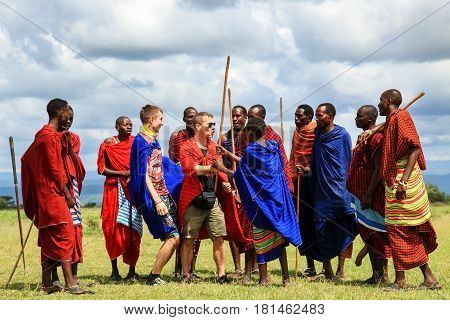 Africa Tanzania - February 2016: European tourists interact with the indigenous inhabitants of Africa in the village of the Masai tribe.