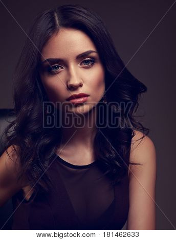 Sexy Young Makeup Model In Brown Dress And Curly Hairstyle Posing On Dark Shadow Background. Closeup