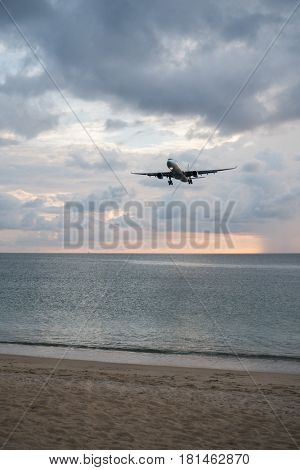 View from the sandy beach on the landing airplane isolated above the sea over beautiful cloudy sky background