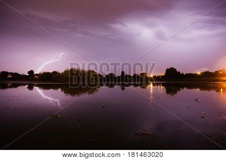 Bolts of lightning over the river. Thunder Sky. The beautiful night scenery. Slow shutter speed. The spectacular sky. Scenic view. The surface of the water. Lightning in the sky. Lightning above the water. Lightning during a thunderstorm