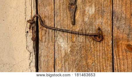 old rust hook on wooden door