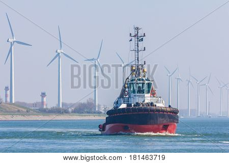Rotterdam the Netherlands - April 9 2017: tug boat and wind turbines in Rotterdam harbor